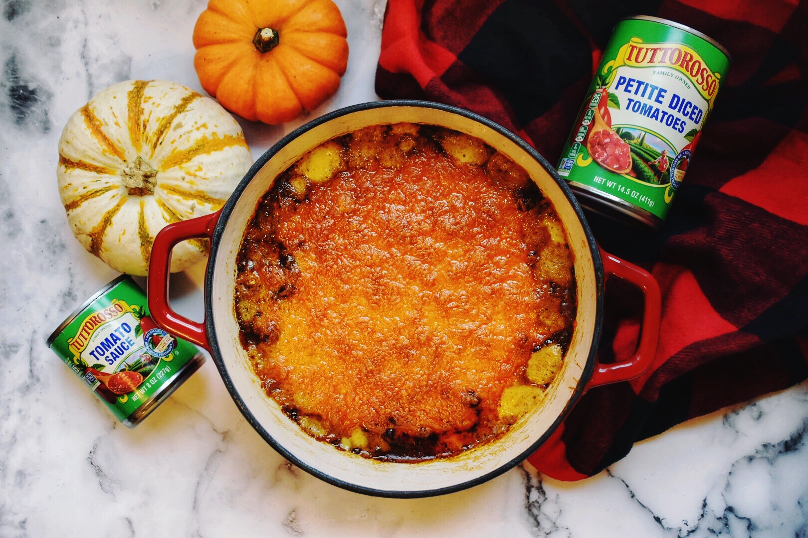 Cheesy Chili Macaroni with a buffalo plaid scarf, marble backgroud, Tuttorosso tomatoes can, and 2 pumpkins.