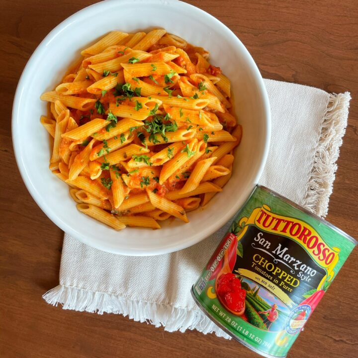 Bowl of penne pasta with dairy-free vodka sauce on a wood table with cream colored cloth and a can of Tuttorosso tomatoes next to it.