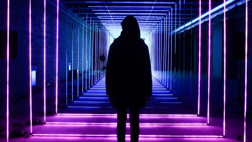 Image of a shadowy figure standing in a neon-lit hallway.