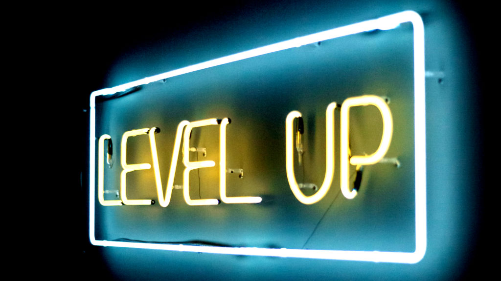 Neon sign that says Level Up in blue and yellow light - level up your page and keyword rankings with this list of the best free SEO tools