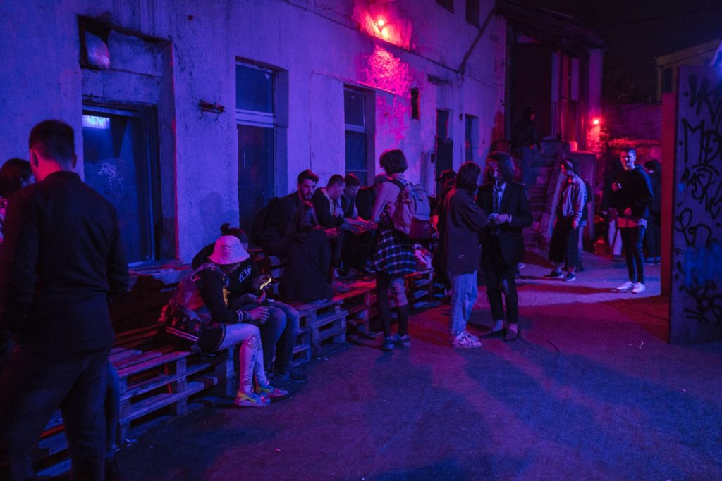 Neon lighting shining on a group of young people in trendy clothes standing and sitting on benches in an alleyway and casually socializing with each other or on their smartphones, as a visual example of the benefits of waitlists for product launch marketing campaigns