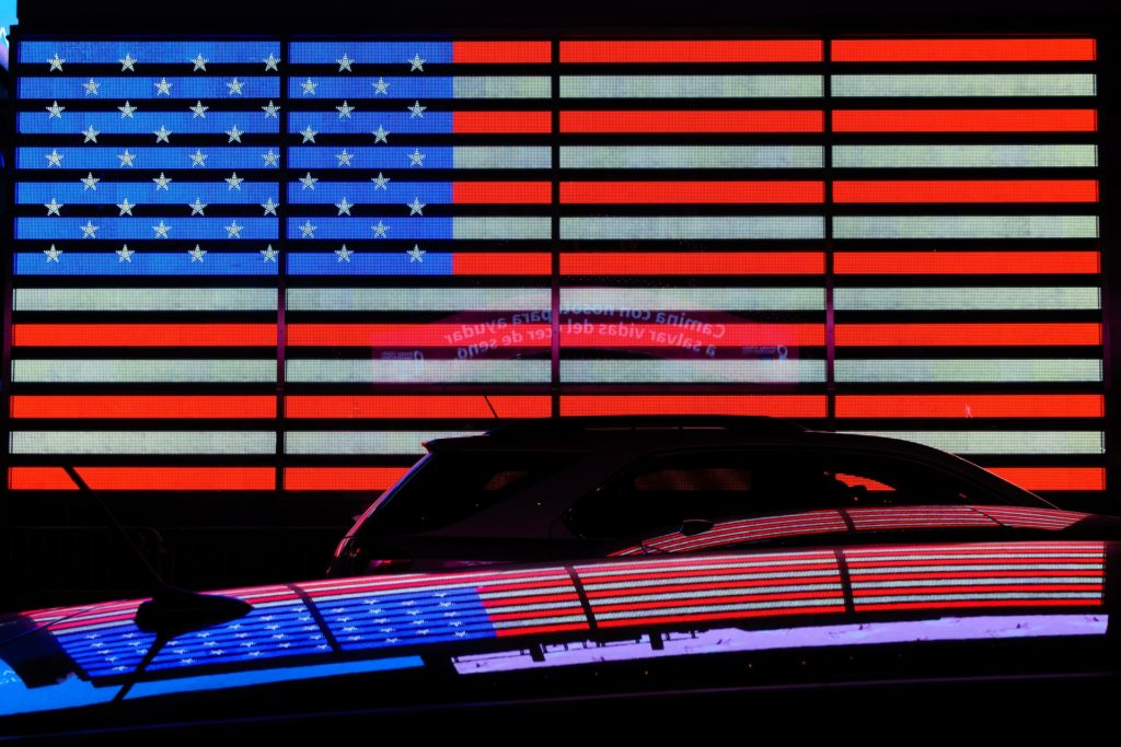 Cause marketing & brand trust: image of a neon U.S. flag and its reflection mirrored on the black silhouette of a car in the foreground