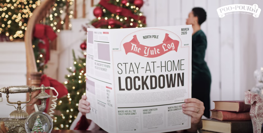 Santa reading a newspaper named The Yule Log with headline Stay-at-Home Lockdown and a black woman as Mrs. Claus in the background decorating a Christmas tree from the Pou-Pourri holiday marketing campaign