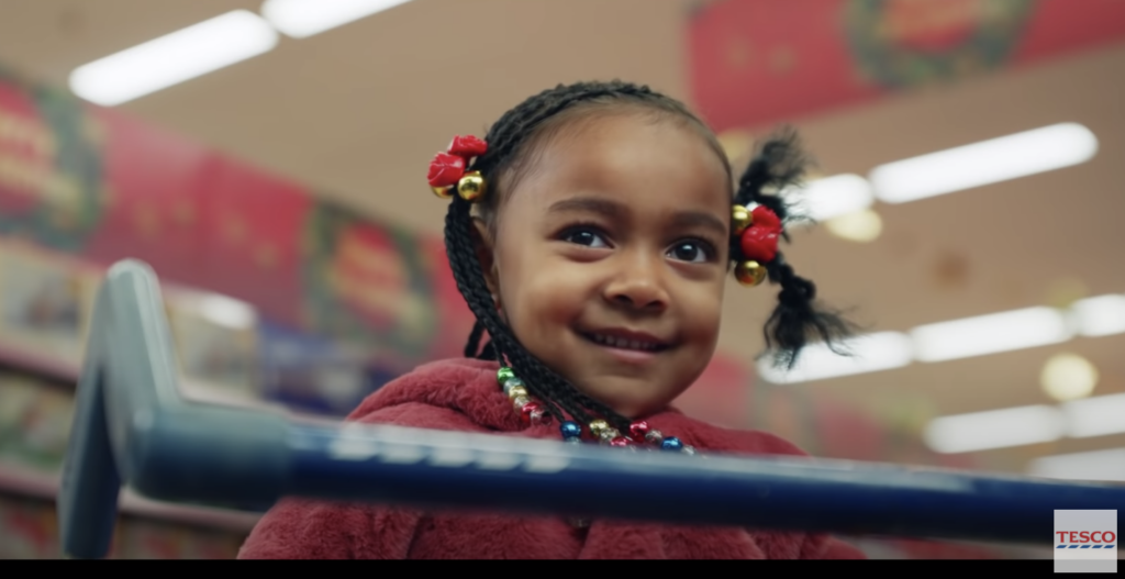 A young black girl smiling mischievously in a shopping cart at UK grocery store Tesco