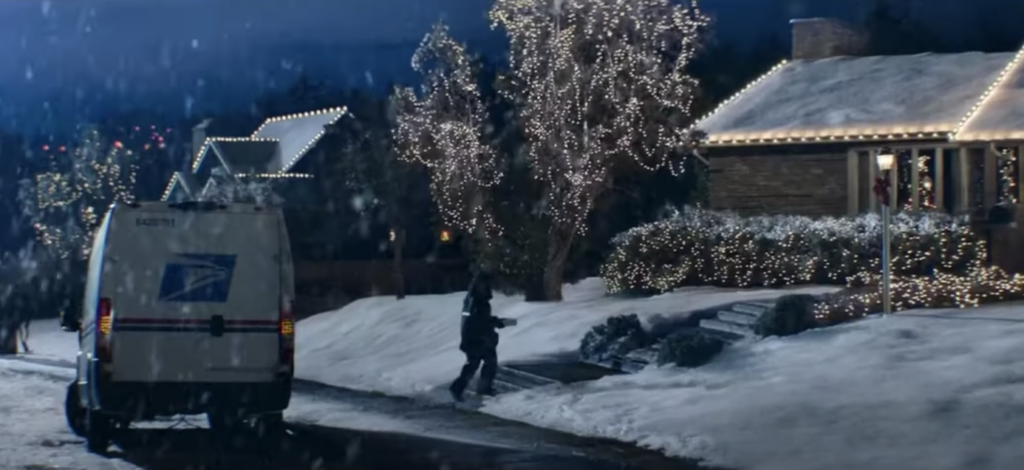 a USPS truck parked outside a home decorated with Christmas lights with snow everywhere. a still from the USPS holiday marketing campaign ad 2020