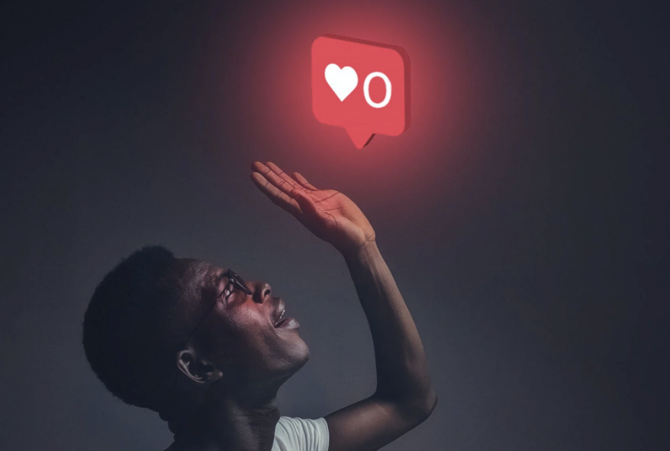 image of Black man below a glowing neon sign showing heart symbol and a 0 to represent 0 likes on social media, as part of the article on how influencer marketing reflects a social media diversity issue