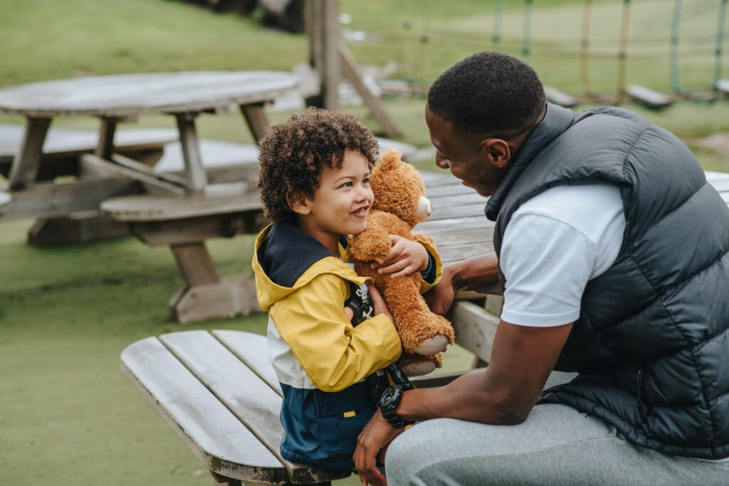 image of a little brown skinned boy holding a teddy bear and looking adoringly up at a sweetly smiling black man, presumably his father, while they sit on picnic table benches outdoors