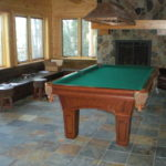 basement pool table room with fireplace