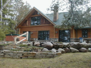Exterior from lake, stone landscaping