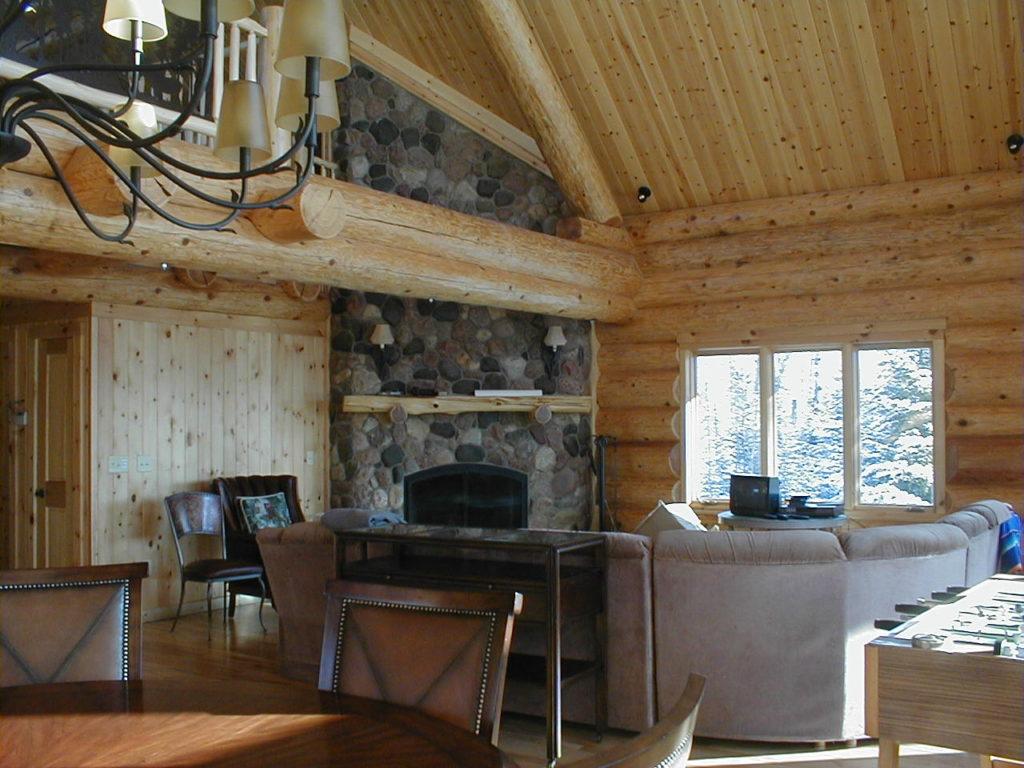 Living room stone fireplace, log walls