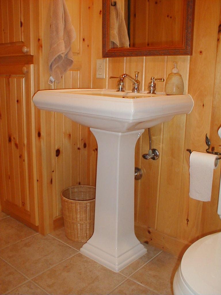 Pedistal sink, pine walls, tile floors