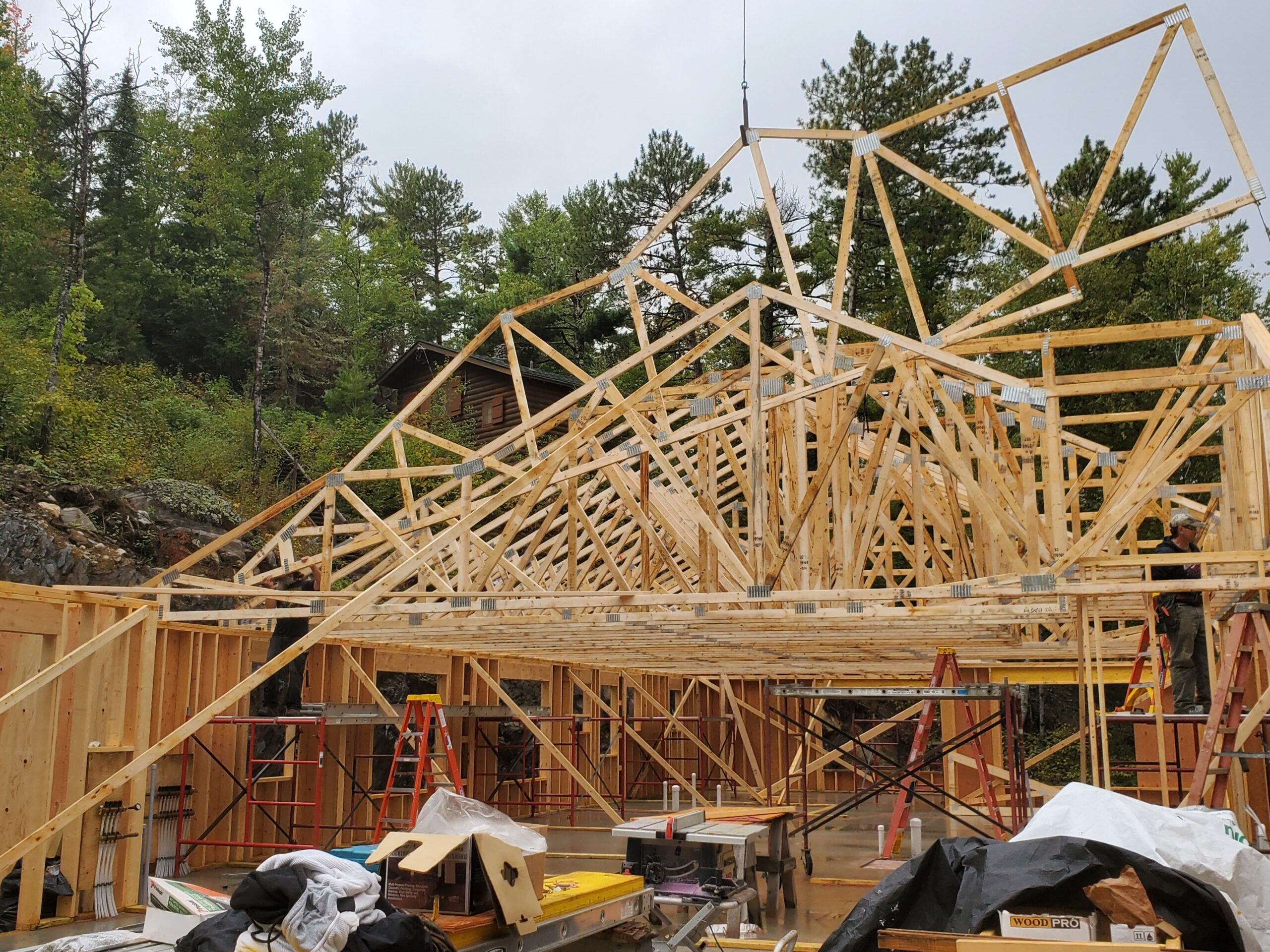 Crane setting trusses, custom home by Huisman Concepts
