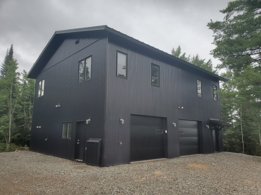 Large garage with steel siding and roof, shop below and living/studio space above