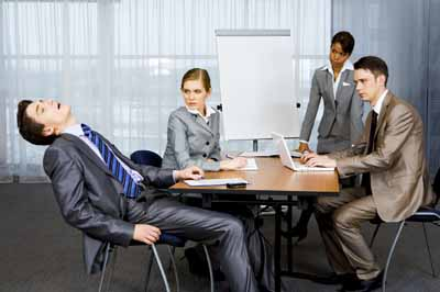 Photo of displeased businesspeople looking sternly at snoring man at presentation