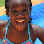 girl with big smile on her face going down waterslide