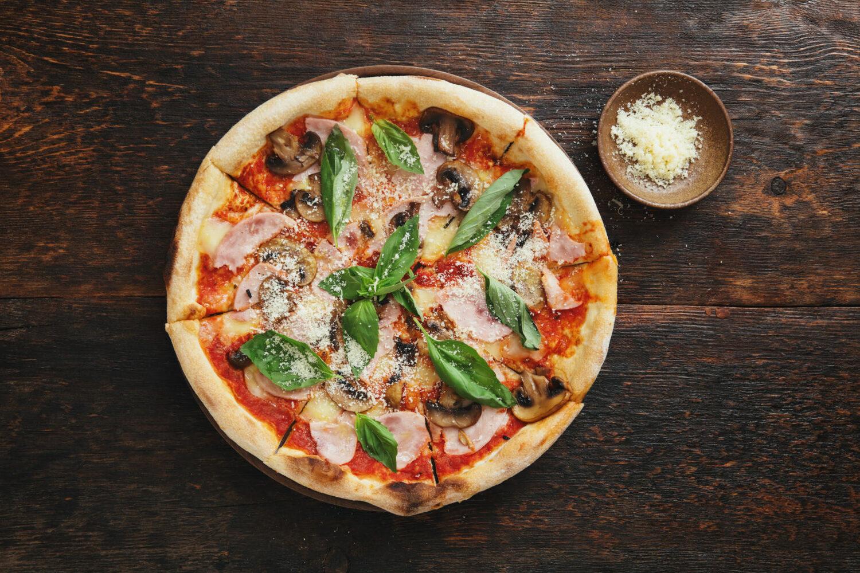 Pizza with ham, mozzarella, mushrooms, herbs