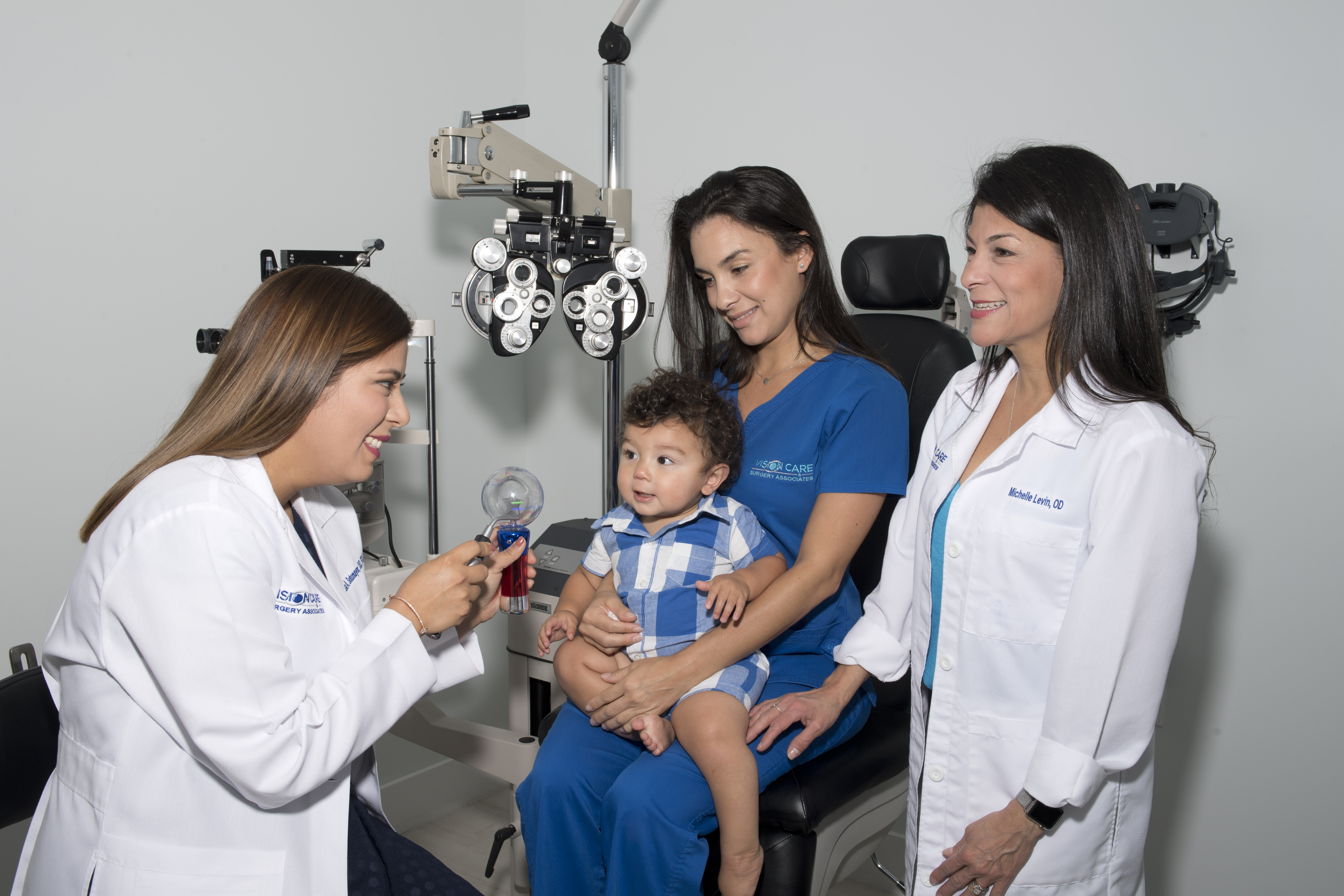 Mom holding baby as two eye care professionals work with him
