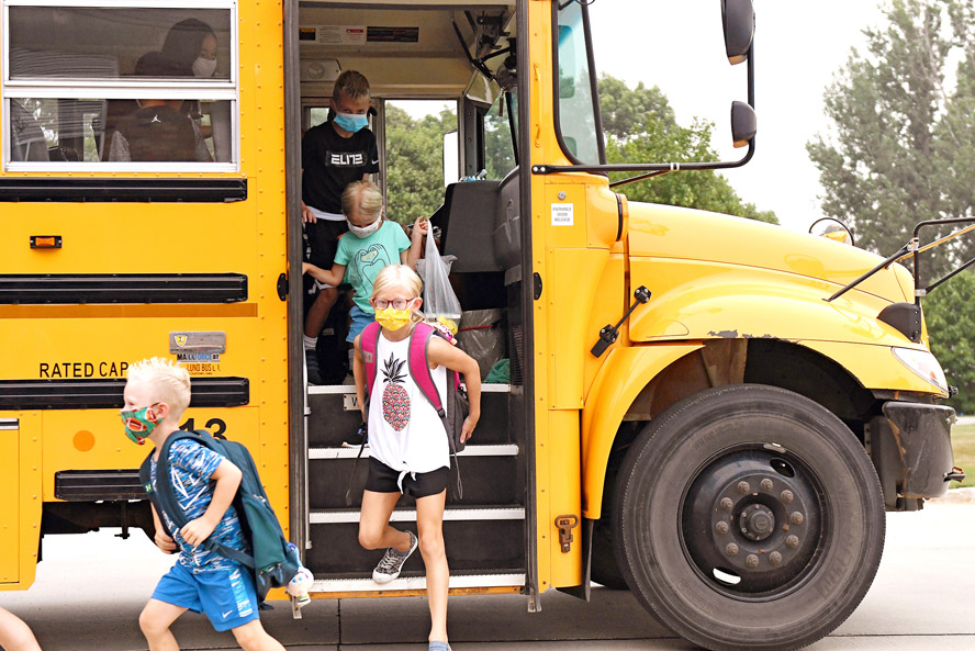 Kids getting off school bus with masks in pandemic