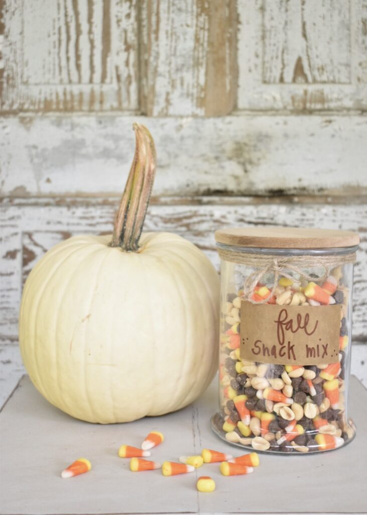fall snack mix with candy corn, peanuts and chocolate chips in a glass jar with a wooden lid