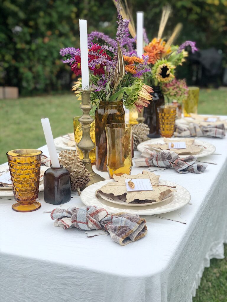 fall tablescape set up outdoors, with amber vases for flowers and candles, white plates, layered with a large dried wreath, amber vintage goblets and brown plaid napkins