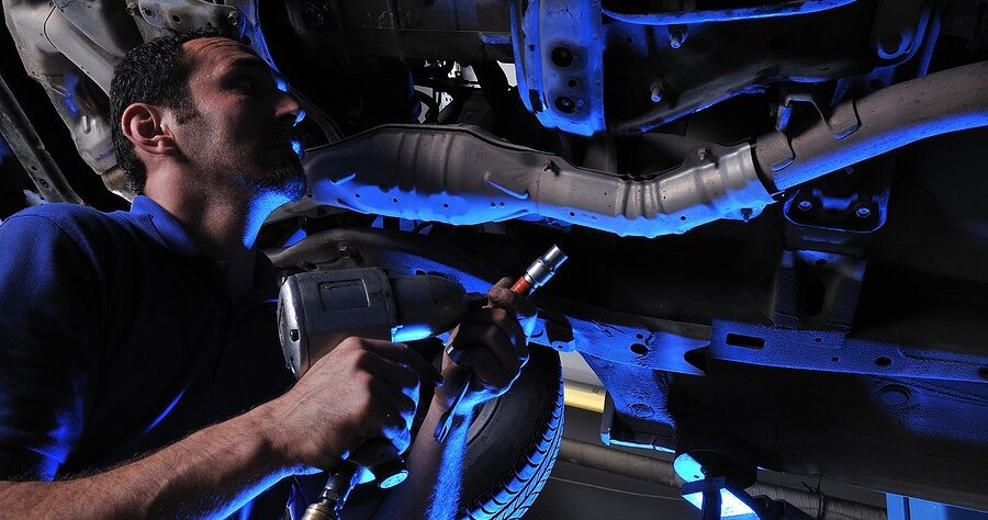 Auto Repair Services in Cleveland Heights, OH image of mechanic with tool under car on lift with blue light in background