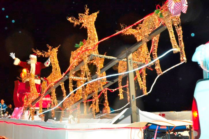 Santa on a fake slay with christmas tree light reindeer in front