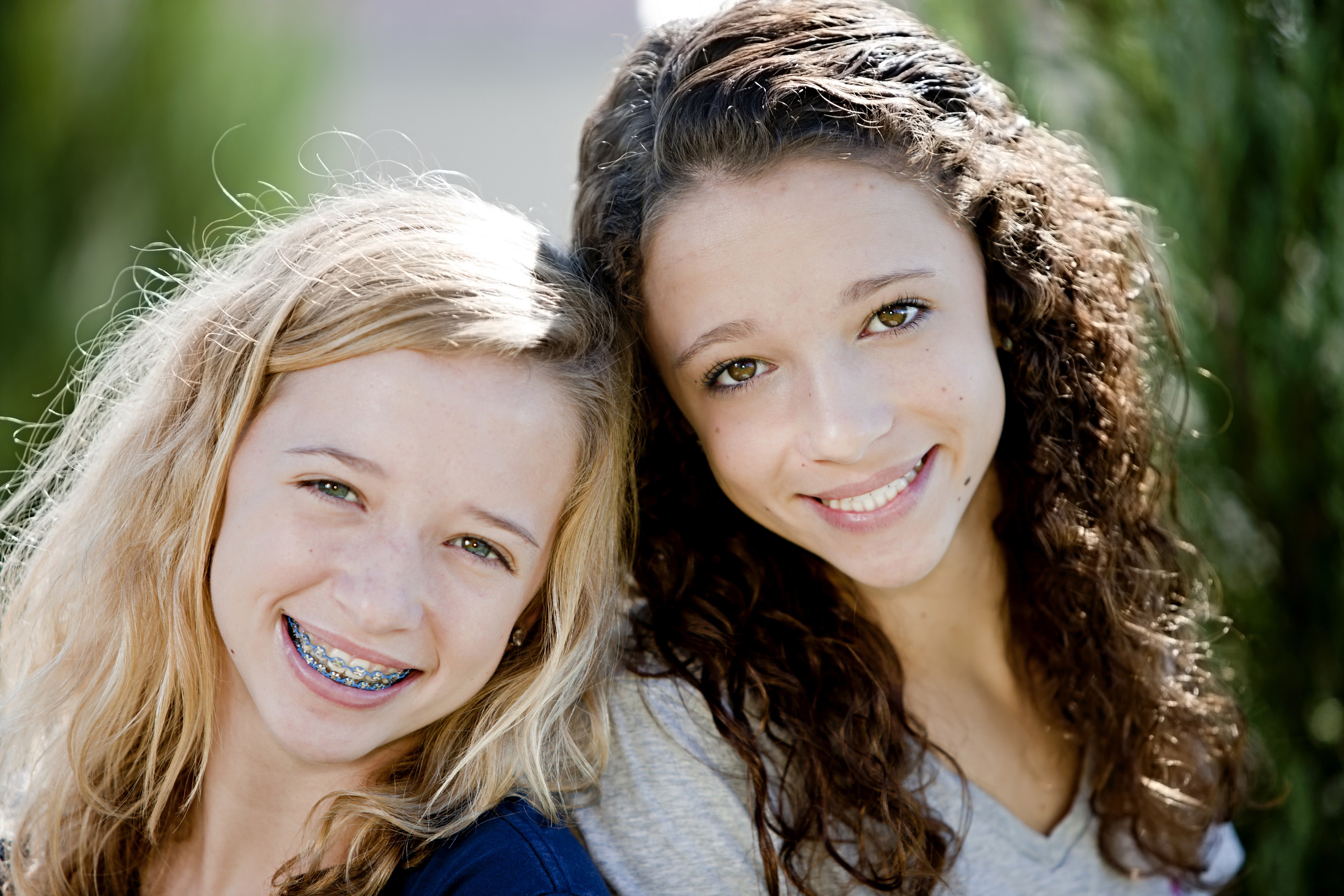 A head and shoulders image of two smiling caucasian real teenage girls. The girls are 13 year old twin sisters. The image is outdoors on a sunny day in the park. Extreme shallow depth of field,