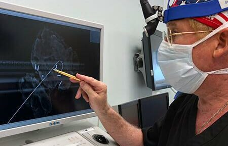 Dr. Robert Donoway scanning an image on a monitor in the surgical suite.