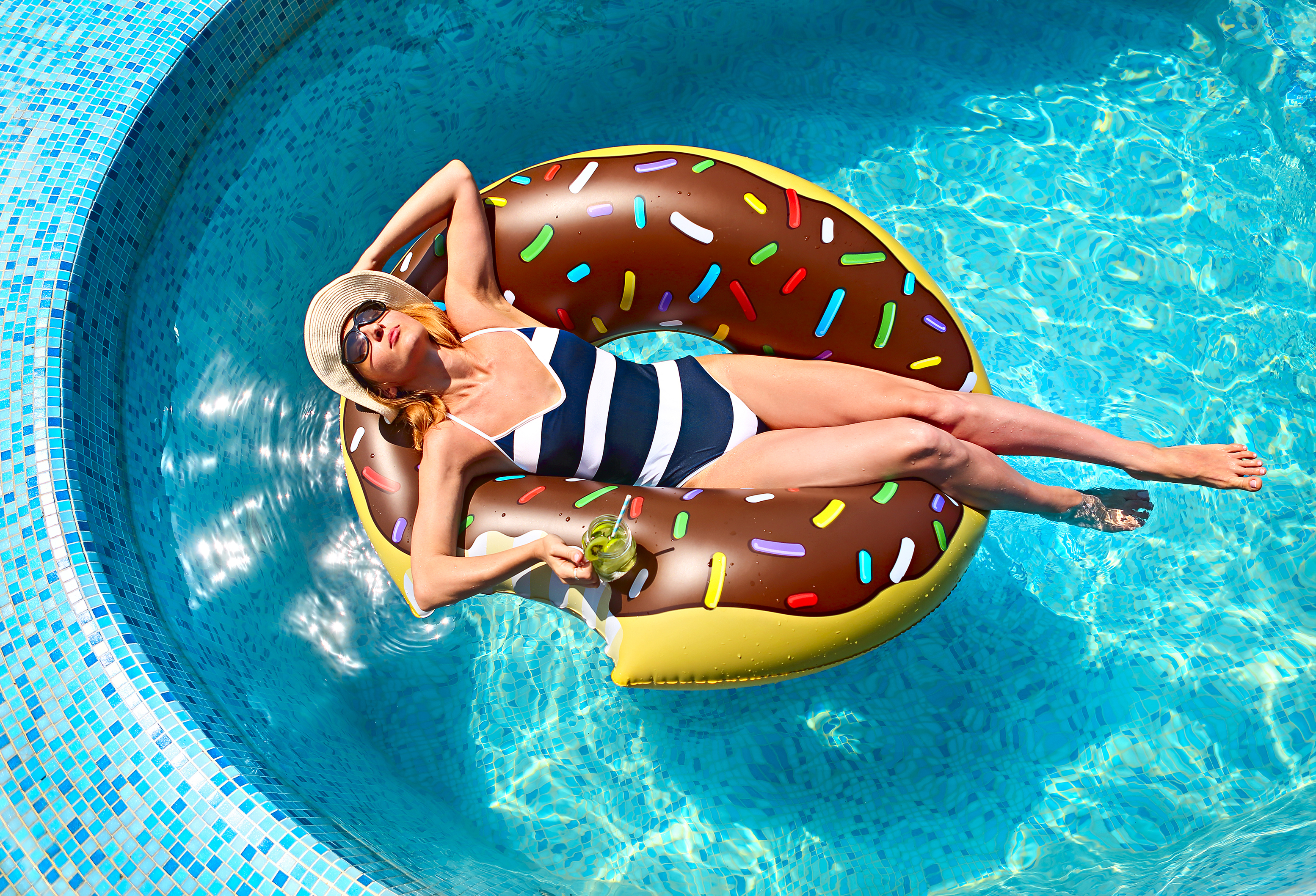 Young woman on summer pool party in swimming pool drinking lemonade