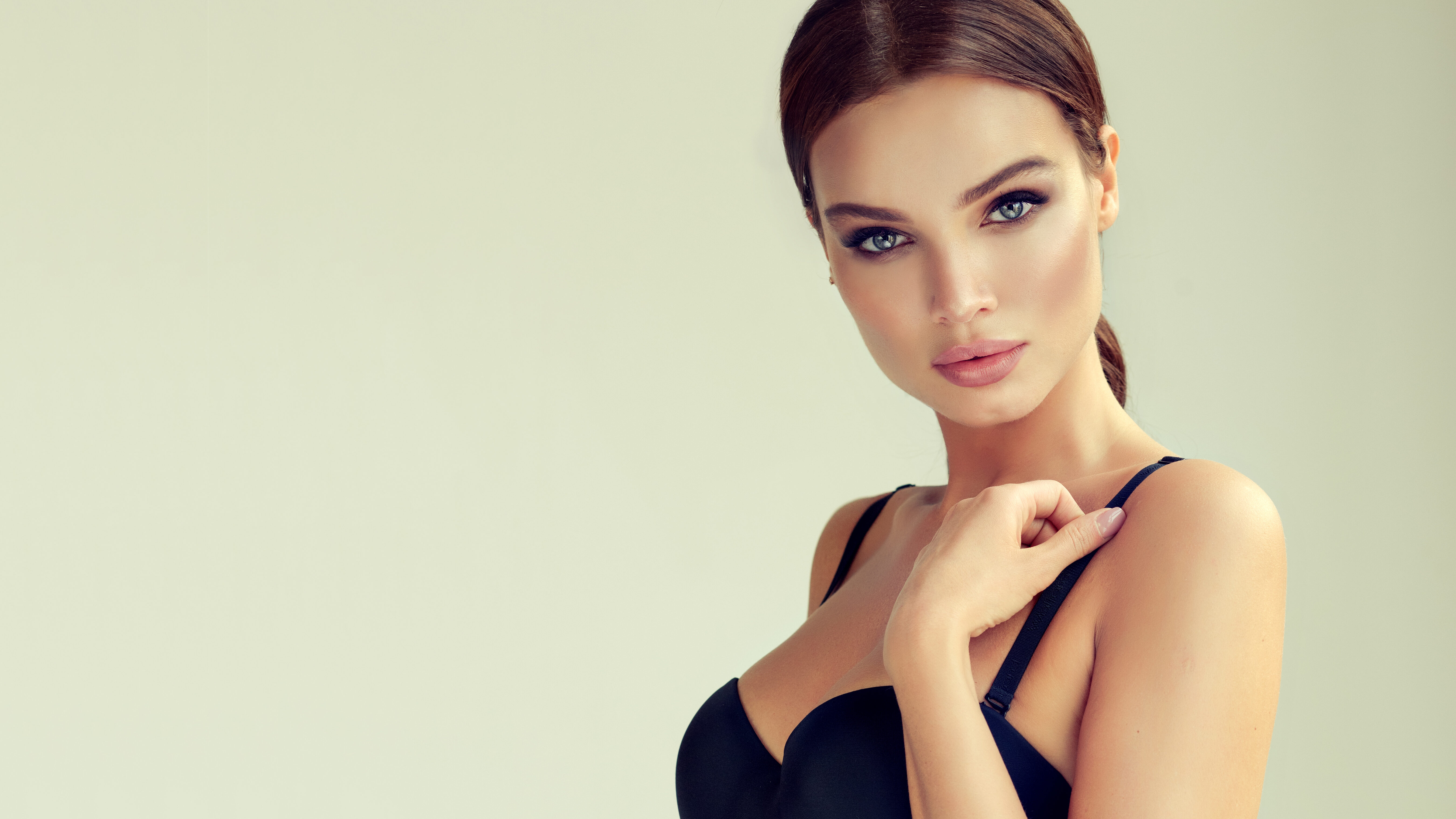 Portrait of young, beautiful woman dressed in seductive black body. Tender and tempting look on viewer. Smokey-eyes style bright makeup and hair gathered in a tuft. Makeup and cosmetology.