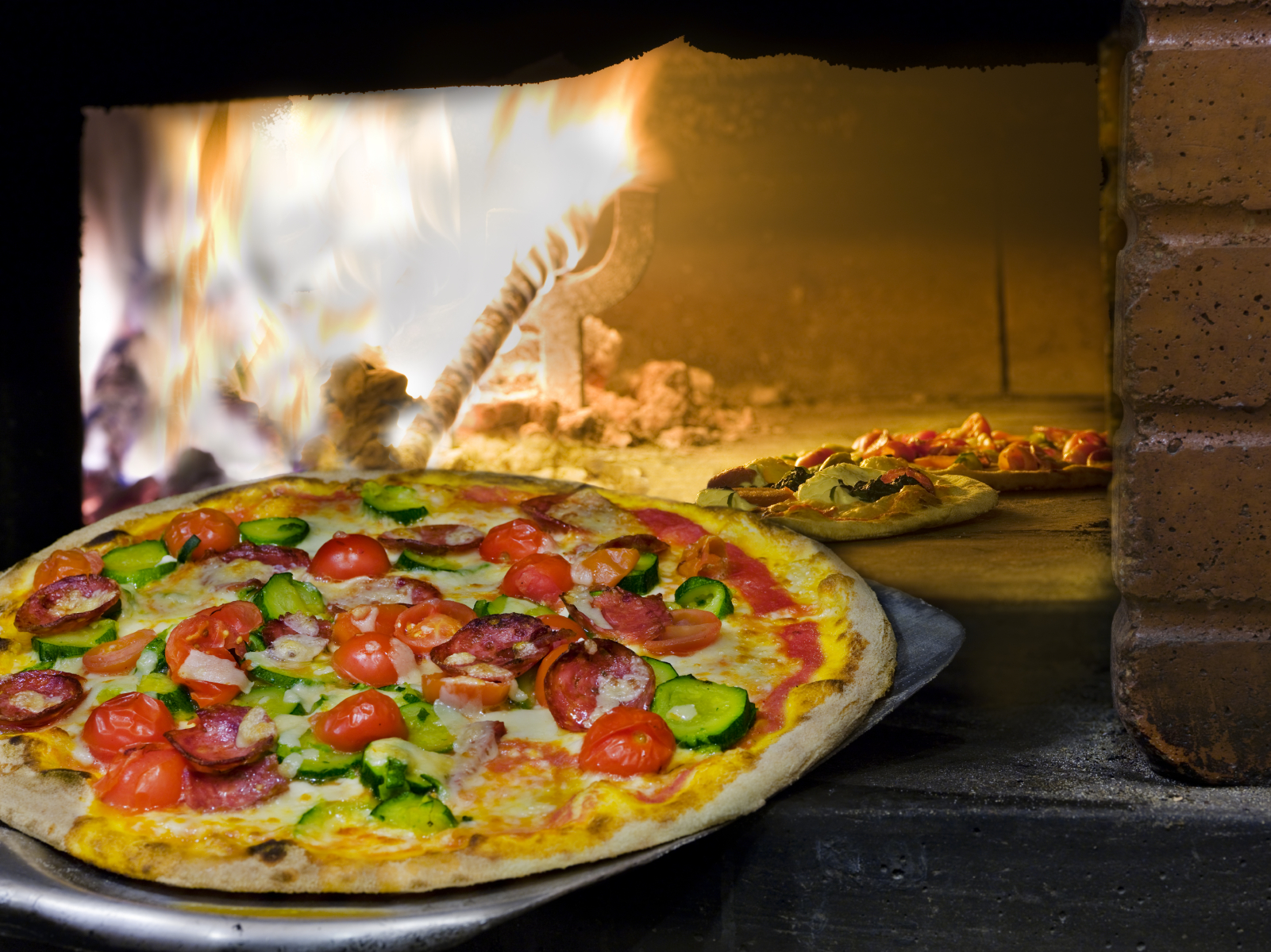 the very italian pizza coming out of a wood burning pizza oven.