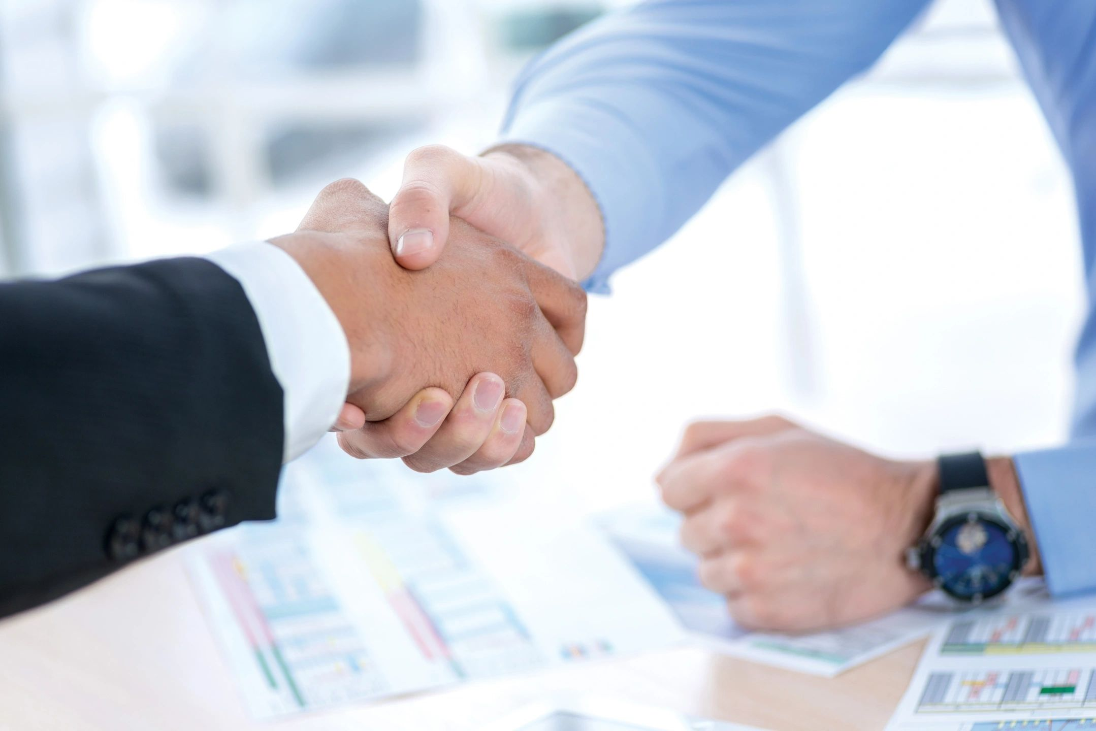 Hands shaking over business documents