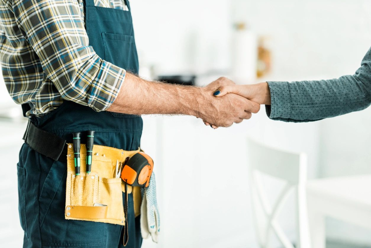 handyman shaking hands with woman