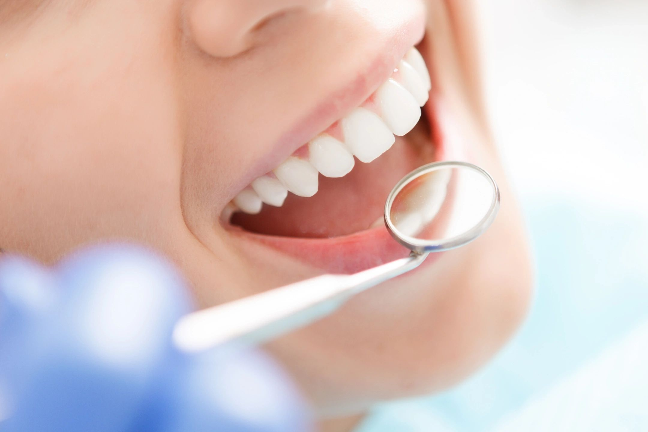 Dentist looking at perfect teeth with mirror instrument