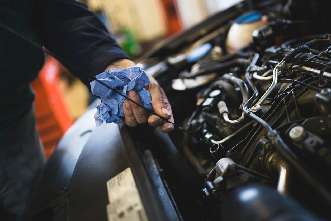 Auto mechanic's hands checking fluids in an engine