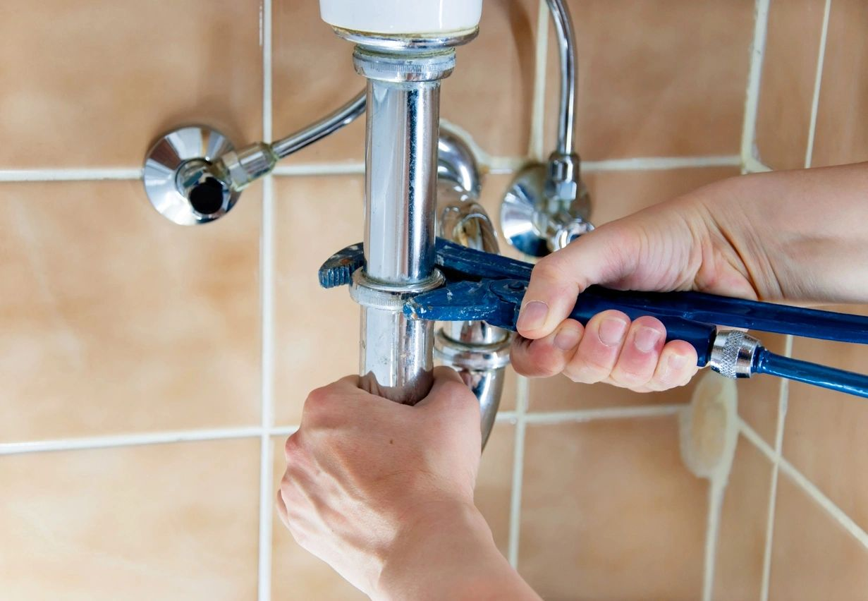 Wrench turning to fix a sink drain