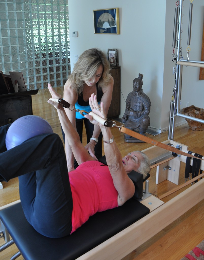 Image of woman teaching another woman Pilates in a studio.