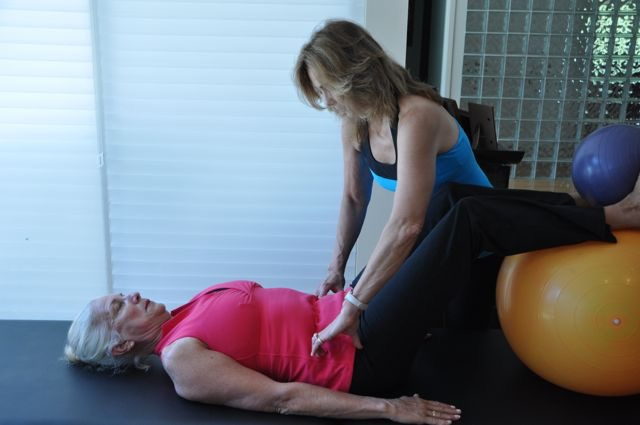 Image of a woman helping another woman with Pilates rehab in a studio.