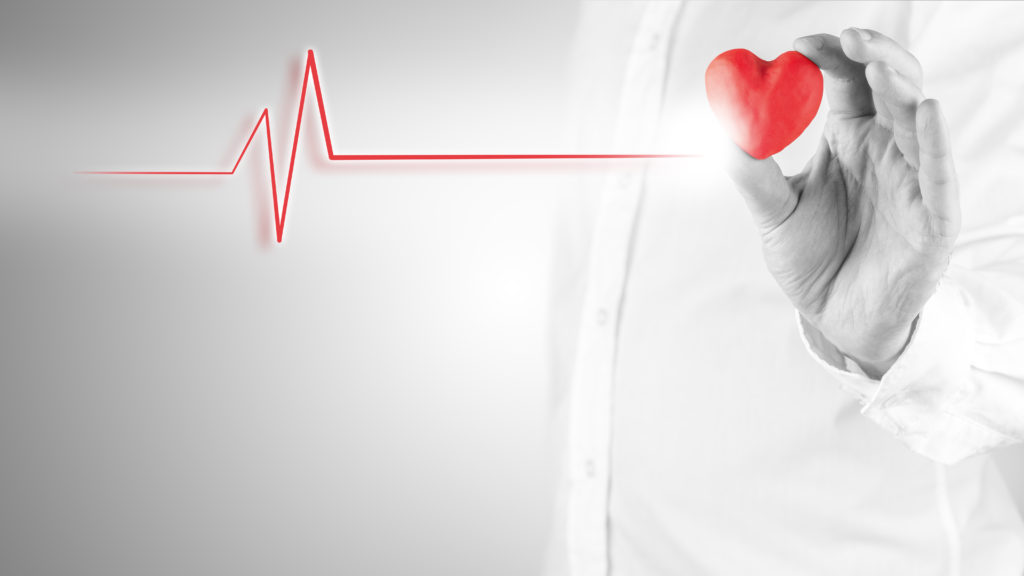 Healthy heart and cardiology concept with a cardiogram linked to red heart.