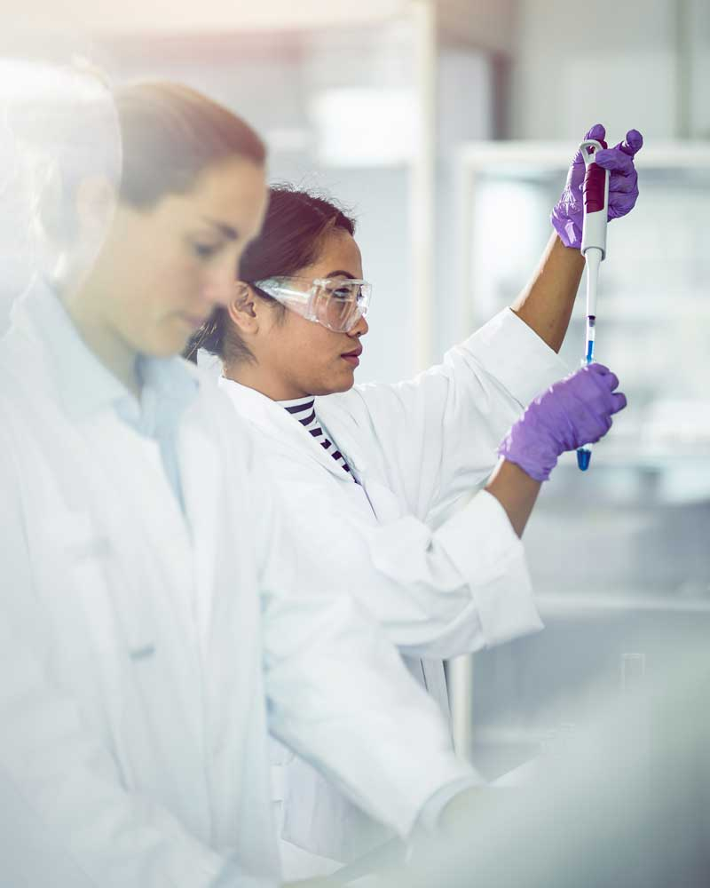 women in lab testing with test tube