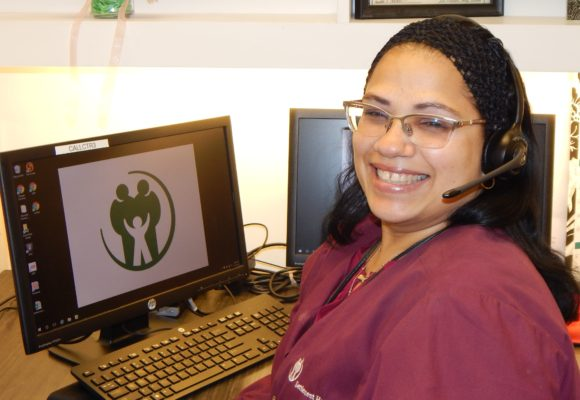 female customer service agent smiling in front of computer with headset