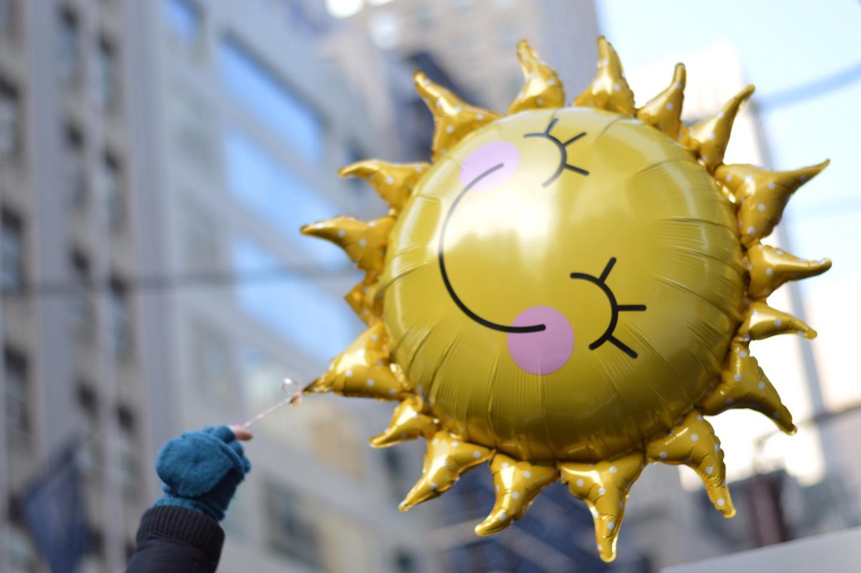 A hand holds a sun-shaped balloon.