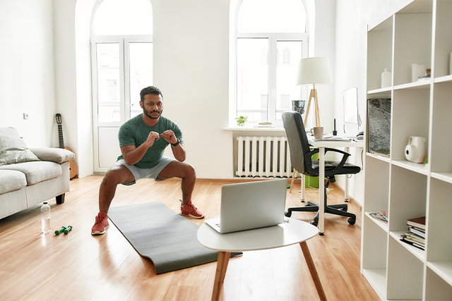 Man working out at home with laptop