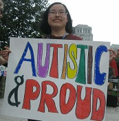 """Young East Asian person holding a sign with the words """"Autistic and Proud""""."""