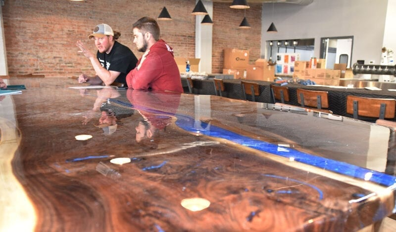 The restaurant centerpiece is a 20-foot walnut island with a river-like blue streak running through it. The piece — as well as a similar 24-foot bar top — was handmade by UTOG Brewing partner Jack Hubble.
