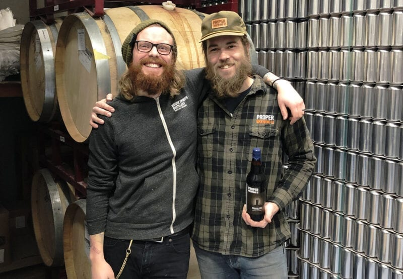 Brewers Jeff Bunk, left, and Jack Kern release Proper Brewing Co.'s first barrel-aged beer — Monolith.