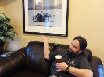 Bonneville Brewery's head brewer Dave Watson enjoys a pint below a famous photo of Salt Flats motorcycle racer Rollie Free.