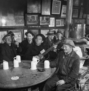 """Woody Guthrie singing at McSorley's Bar, NYC, 1943 - the sign on his guitar reads """"This Machine Kills Fascists""""."""
