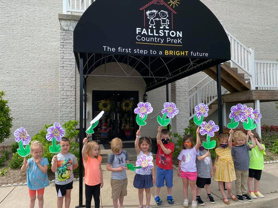 Students holding flower in front of school