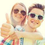 smiling teens piggybacking in sunglasses 2